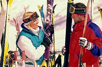 Young couple holding skis and ski poles