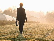 Italy, Piedmont, businessman walking in frosty meadow near greenhouses