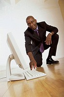 Businessman squatting on the floor looking at a computer monitor