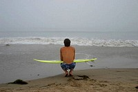 Rear view of a young man squatting with a surfboard at the beach