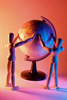 Close_up of two wooden dolls near a globe