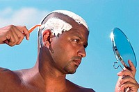 Close_up of a young man shaving his head