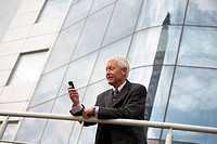 Low angle view of a businessman leaning on a railing and text messaging on a mobile phone