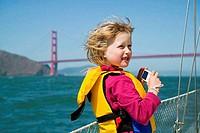 Side profile of a girl holding a camera, Golden Gate Bridge, San Francisco, California, USA