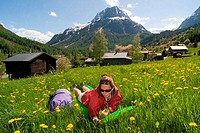 Woman lying in a flowers field, French Alps, France