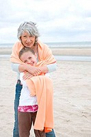 Mature woman hugging her granddaughter from behind on the beach