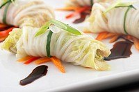 Cabbage roll appetizers with soy sauce garnish