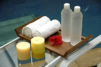 candles burning near rolled towels and water bottles