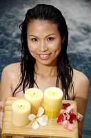 Close_up of a woman holding candles and flowers