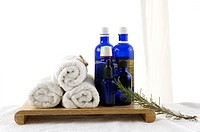 Massage oil bottles near bundles of towels