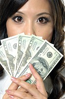 Woman with dollar bills in front of her face