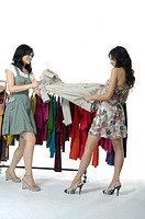 Women pulling a coat in a clothing store