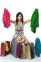 Woman showing clothes near shopping bags and smiling