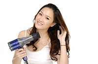 Portrait of young woman using a hair dryer (thumbnail)
