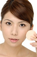 Close_up face of beauty young woman applying face foundation