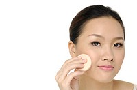 Woman using sponge on face