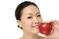Portrait of young woman with apple, isolated on white