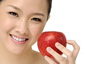 a healthy, beautiful, happy woman is holding an red apple in front of her smiling face
