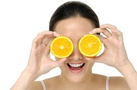 Concept _ Woman with orange slices over eyes