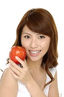 Beautiful asian woman holding an apple isolated on white