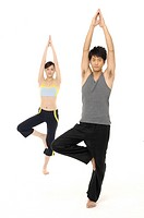 Young Couple doing yoga indoors