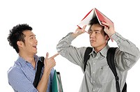 Male university student laughing at his friend holding a book over his head