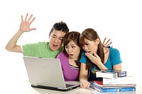 University students using a laptop and looking surprised
