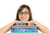 Female university student leaning on stack of books