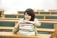 Female university student leaning on a stack of books in a classroom