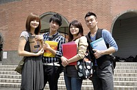 University students holding books and smiling