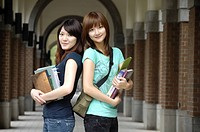 Female university students standing back to back and smiling