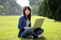 Female university student using a laptop in a lawn