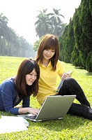 Female university students using a laptop in a lawn