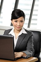 Businesswoman using a laptop in an office (thumbnail)
