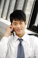 Businessman talking on a mobile phone in an office (thumbnail)