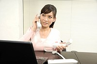 Businesswoman talking on telephones in an office