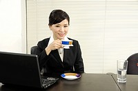 Businesswoman drinking tea in an office