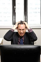 Businessman working on a computer and looking frustrated (thumbnail)