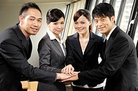 Business executives stacking hands in an office (thumbnail)