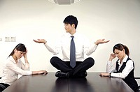 Businessman doing yoga and annoying his colleagues in a conference room