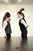 Businesswoman beating her colleague with a high heel