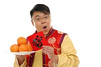 Man holding a Chinese new year couplet and a plate of oranges