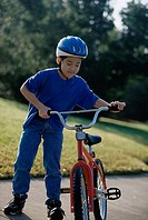 Boy holding a bicycle