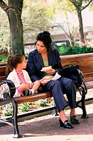 Portrait of a mother and daughter sitting on a park bench