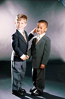Portrait of two young boys dressed as businessmen shaking hands