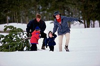 Parents with their son and daughter dragging a Christmas tree in snow