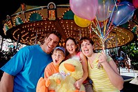 Portrait of parents with their son and daughter in an amusement park
