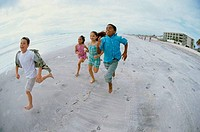 Two boys and two girls running on the beach