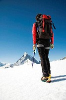Low section view of a hiker walking on snow with a mountain in the background, Matterhorn, Zermatt, Valais, Switzerland