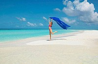 Young woman holding up a sarong running on the beach, Maayafushi, Maldives